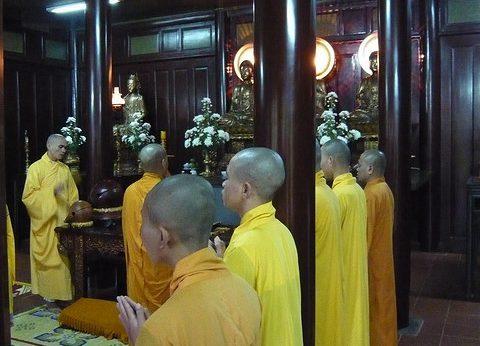 """Călugări buddhişti vietnamezi monks în timpul slujbei în pagoda din Hue, Vietnam. Autor Flickr user """"mrbold_flickr"""", Wikipedia."""
