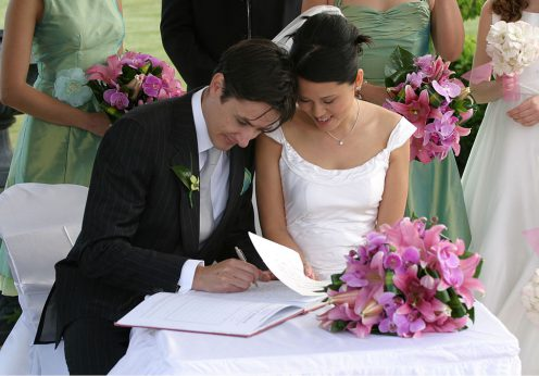 1024px-Bride_and_groom_signing_the_book